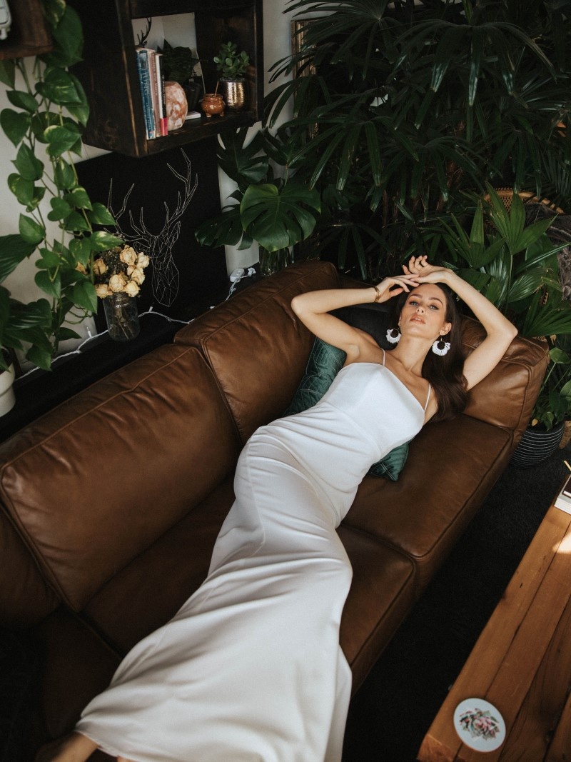Bride in custom made gown lies on couch