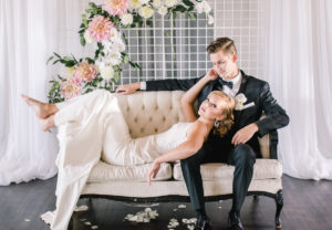 Bride lays her head on groom as they sit on white vintage couch