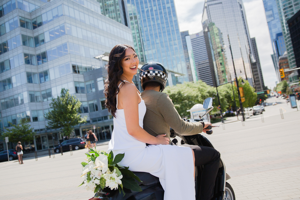 Bride smiles as she is driven on bike down Vancouver streets