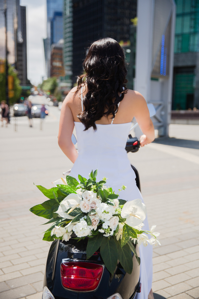 City Chic Bride on bike with bouquet behind her on city street