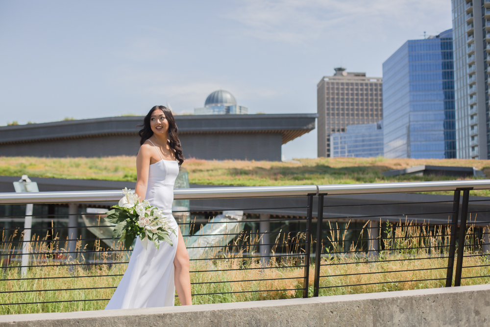 City Chic Bride walks in front of Vancouver Sky