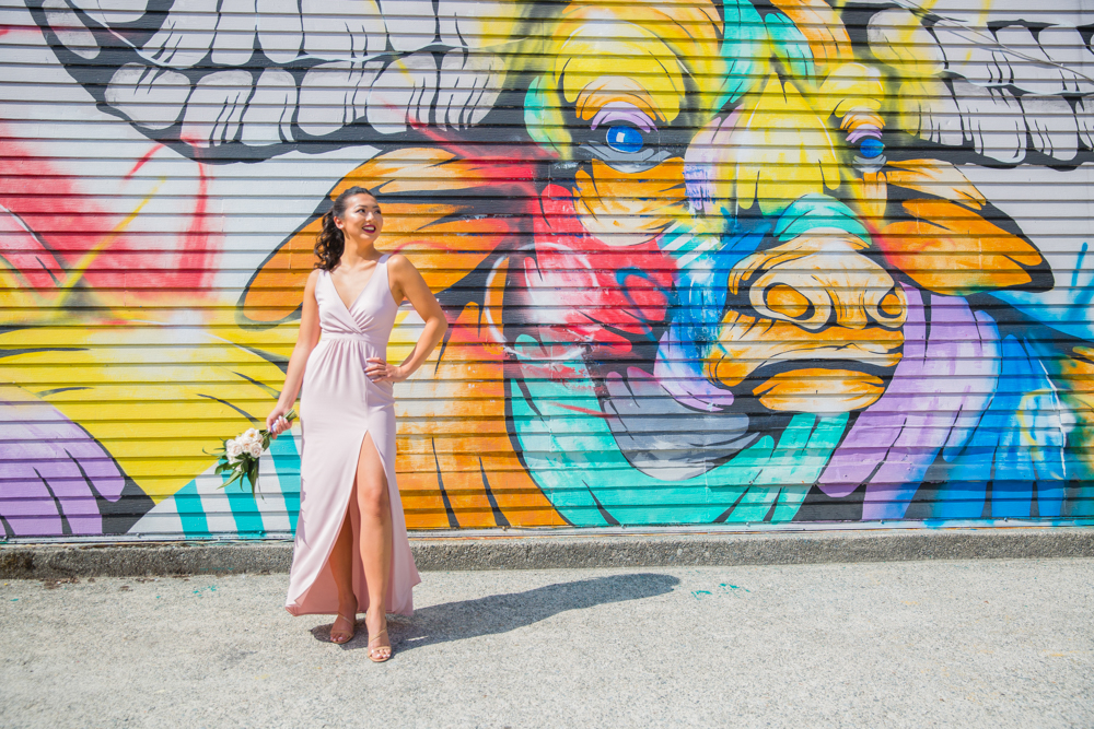 Bride in white gown in front of wall graffiti