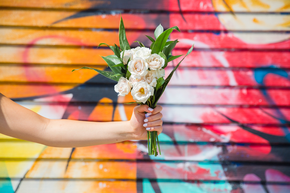 Bridal flowers by Karen Wazny in front of graffiti in Vancouver