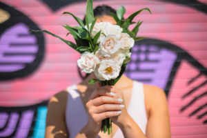 City Chic Bride holds bouquet in front of her face