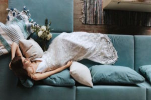 Bride in custom white gown lies on blue couch
