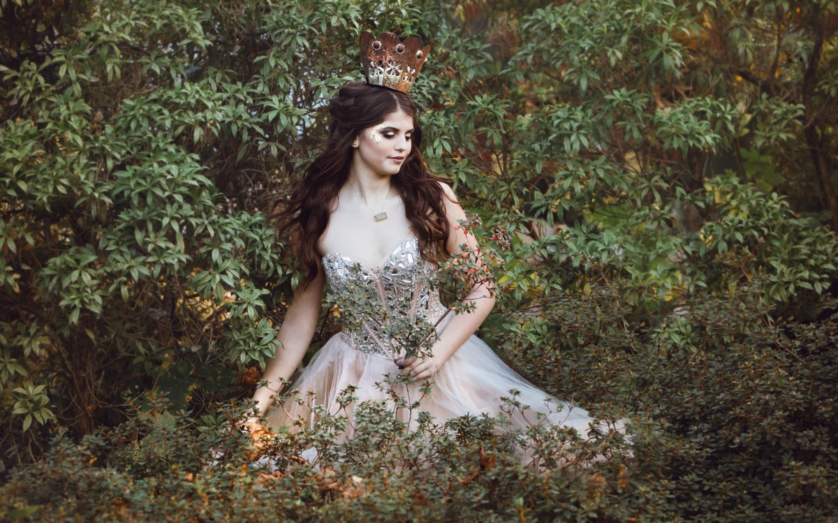 Bride sitting in field in royal inspired gown and long hair