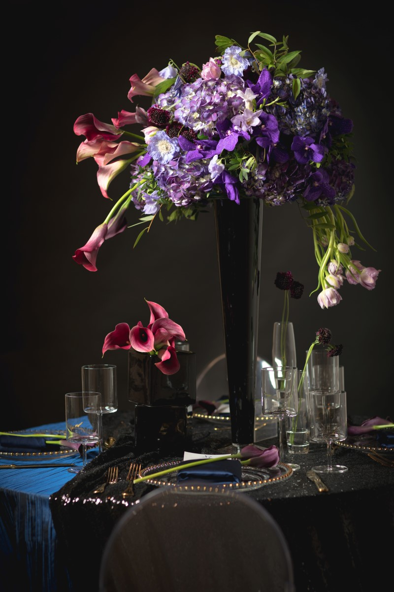 Dark blue linens on wedding reception table and large purple, blue and burgundy floral display