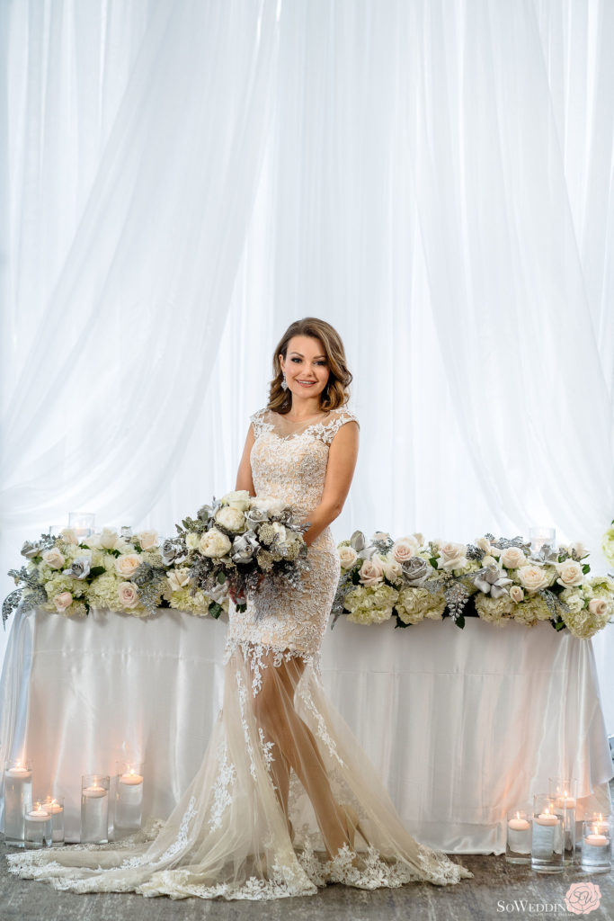 Bride holding silver, blue and white bouquet in front of head table with flower edge by Proline Trading Vancouver