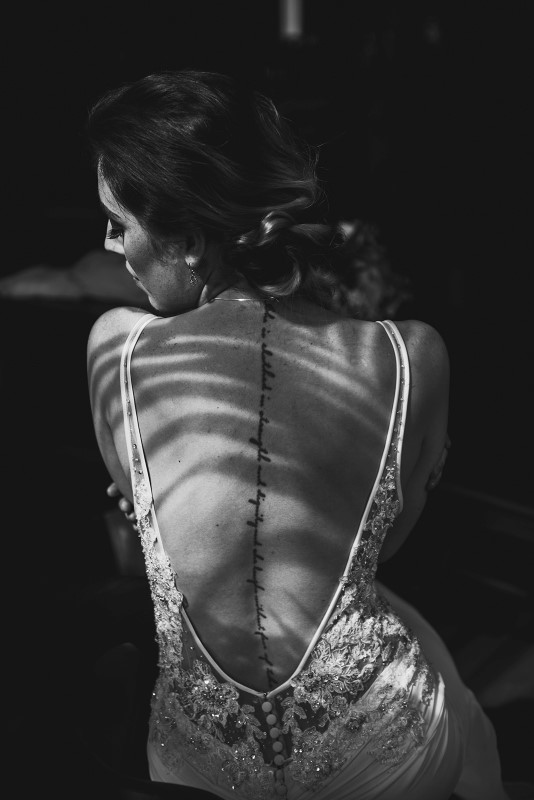 Bride with back tattoo in shadows in black and white shot at Fairmont Empress