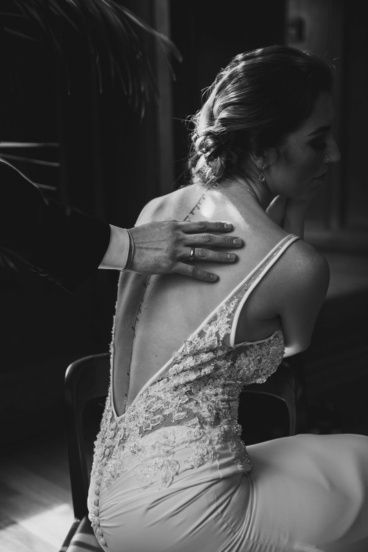 Groom puts hand on back tattoo of bride by KGOODPhoto