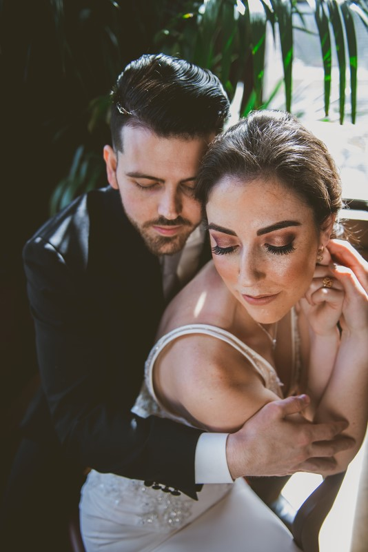 Bride with gorgeous makeup by Artistry by Alexa is held closely by groom at Fairmont Empress