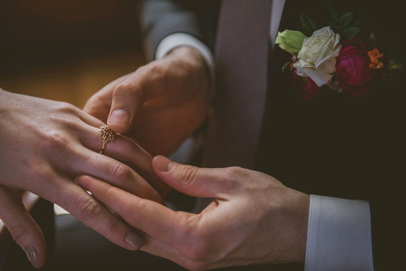 Bride and Groom hold hands looking at ring by Emma Glover Designs on Vancouver Island KGoodPhoto