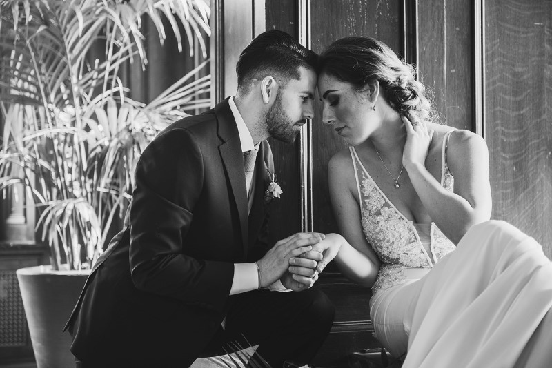 Bride and Groom hold each other's hands in window seat of Fairmont Empress