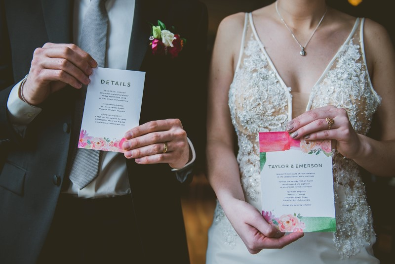 Newlyweds hold pink and coral invite cards by Tickle Tree Designs Vancouver Island