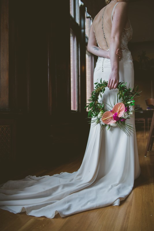 Bride holds hoop covered in greenery and coral flowers by Brown's the Florist