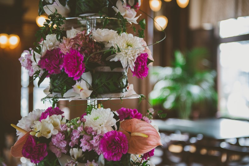 Tropical Empress Wedding Flowers featuring pink and white reception table by Brown's the Florist