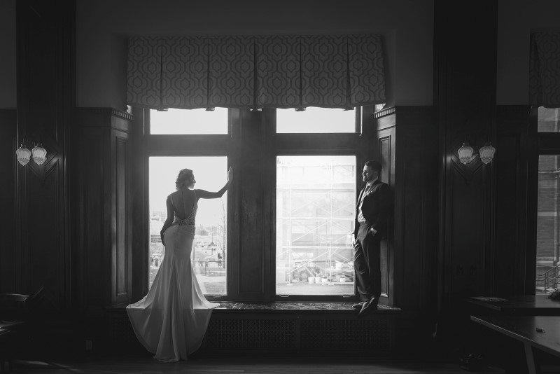 Bride wearing Shades of White Bridal looks out Fairmont Empress Window on Vancouver Island