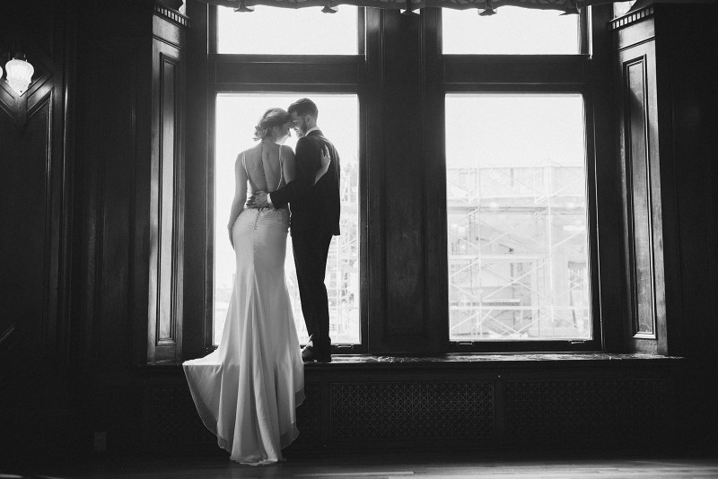 Couple look out Fairmont Empress window by KgoodPhoto