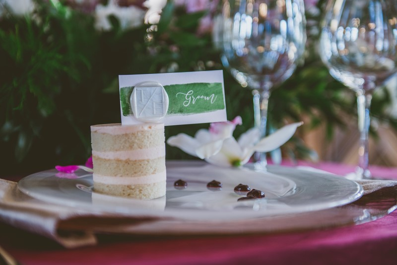 Individual Cake on raspberry place setting and green name card surrounded by tropical flowers Allison Shelrud Cakes Vancouver Island