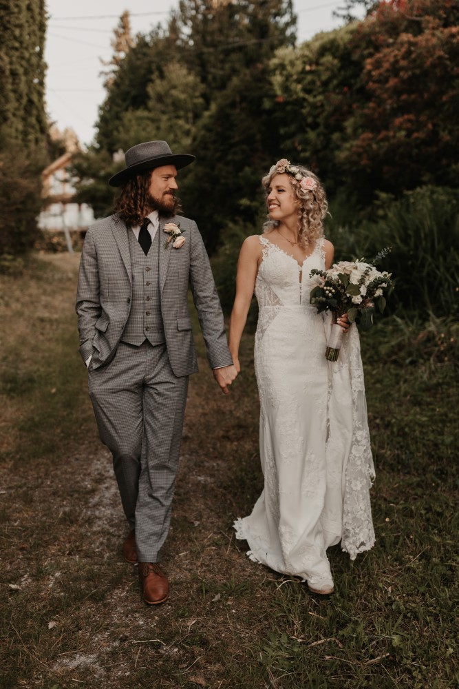 West Coast Weddings Magazine Indochino suit Martina Liana Gown bride and groom walking through forest holding hands floral designs by Coastal Weddings & Events