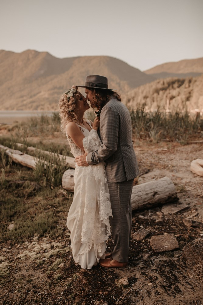 Golden hour Bride and groom touching noses holding each other mountains and sand