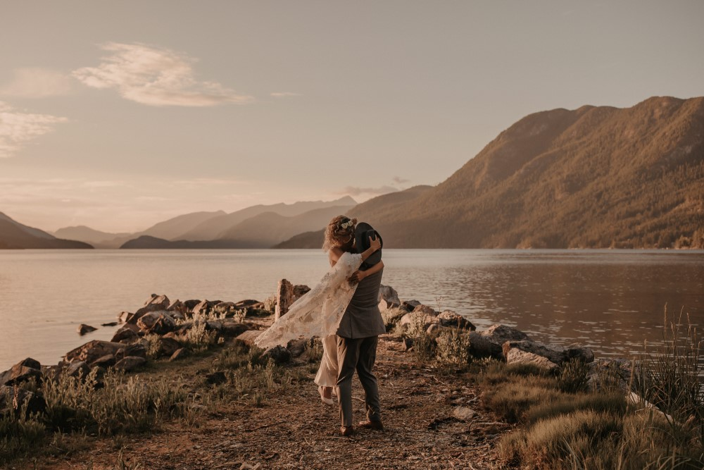 Golden Hour Groom carrying bride by lake mountains in background West coast Weddings Magazine