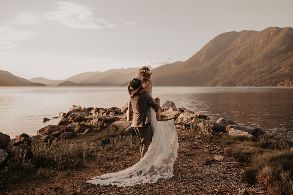 Golden Hour Groom picking up bride with arms around his neck by the lake with mountains Sunshine Coast