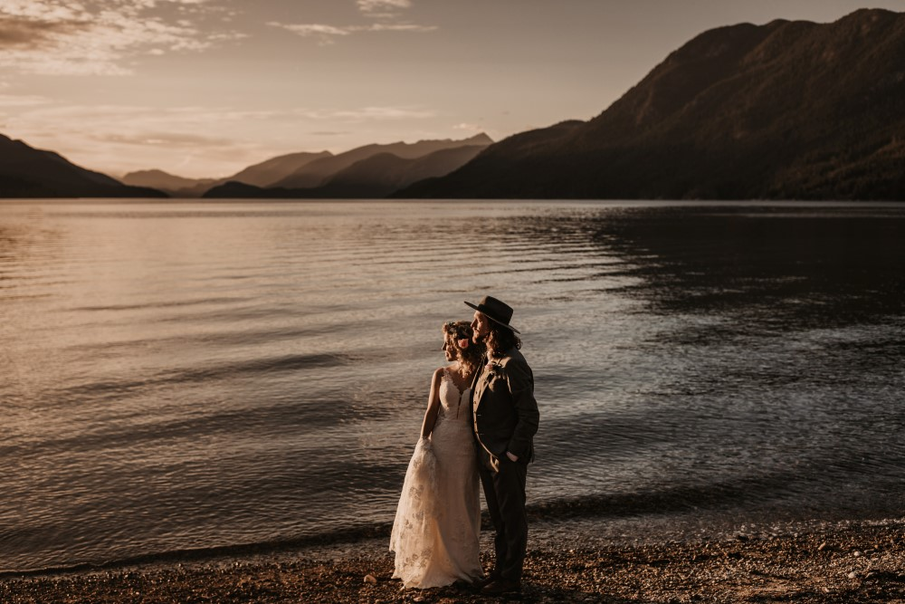 Golden Hour Elopement on the beach by the lake with mountains staring off into the distance Jennifer Picard