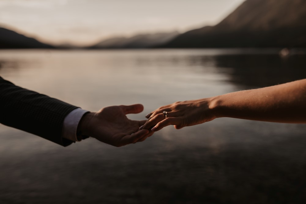 Golden Hour hands touching by lake Jennifer Picard Photography West Coast Weddings Magazine