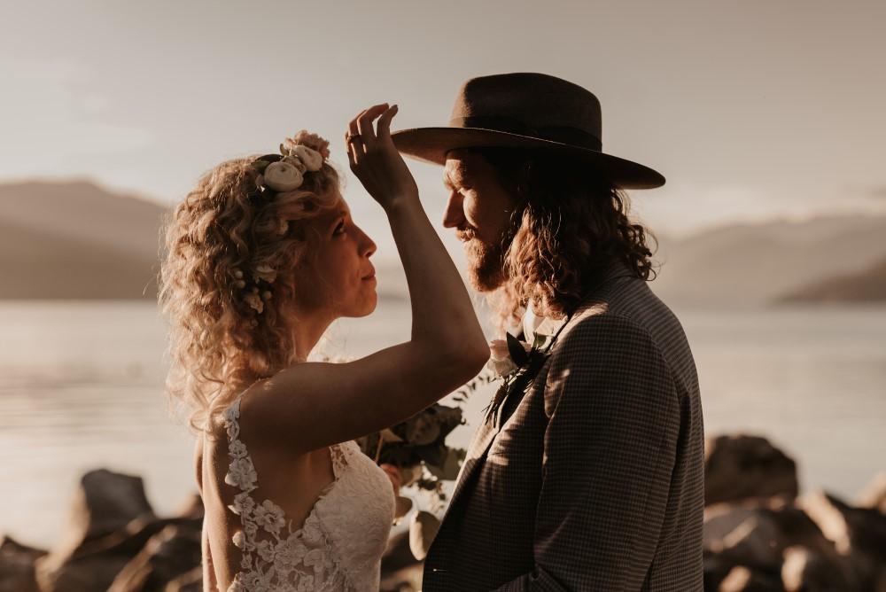 Golden Hour bride touching groom's hat lace dress west coast weddings