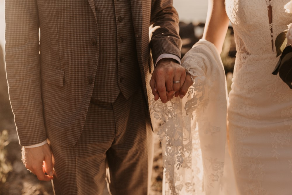 Golden Hour bride and groom holding hands lace dress