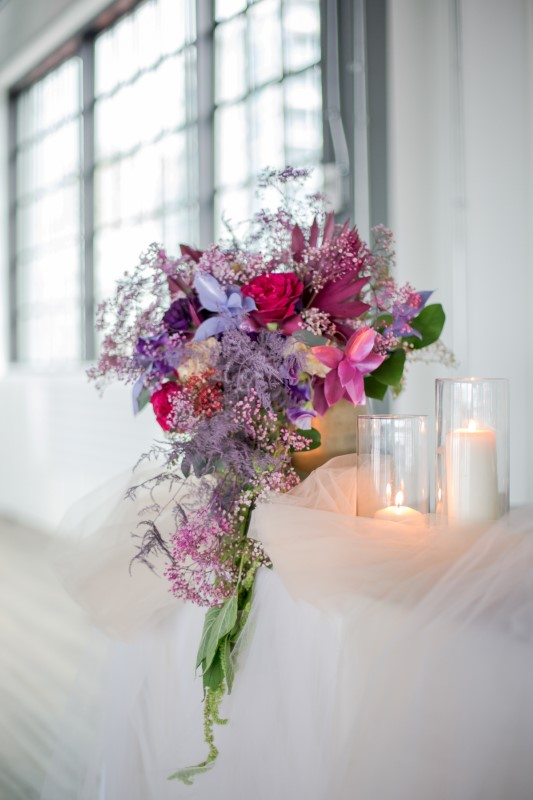 Purple and pink floral arrangement on wedding head table by Karen Wazny in Vancouver