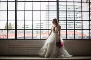Vancouver Wedding Bride looks out window over the city