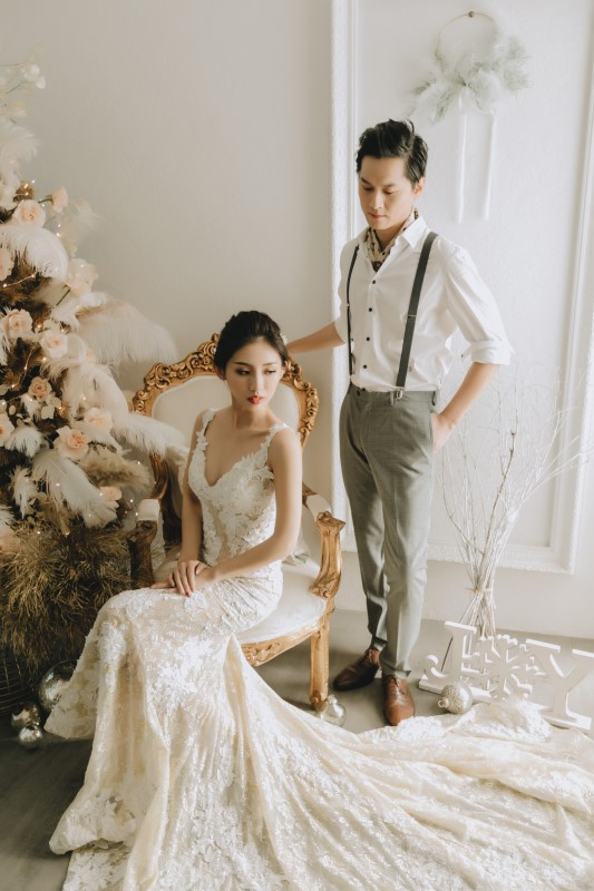 Dreamy White Wedding bride in lacy v-neck gown with long train sitting on chair with groom behind resting his hand on the chair's back