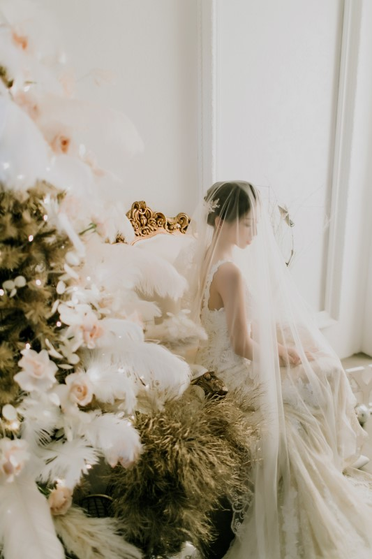 West Coast Weddings Magazine bride indoors next to pine tree decorated with feathers and pink flowers