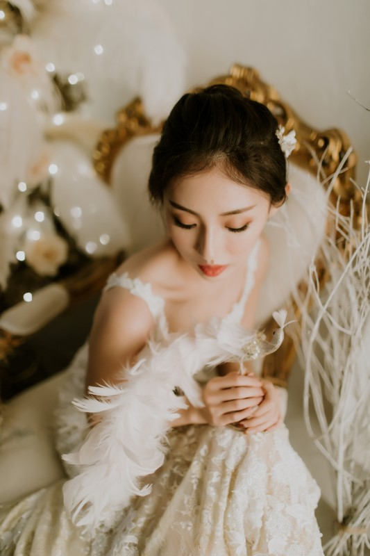 Dreamy White Wedding bride in lace gown with straps holding feathers