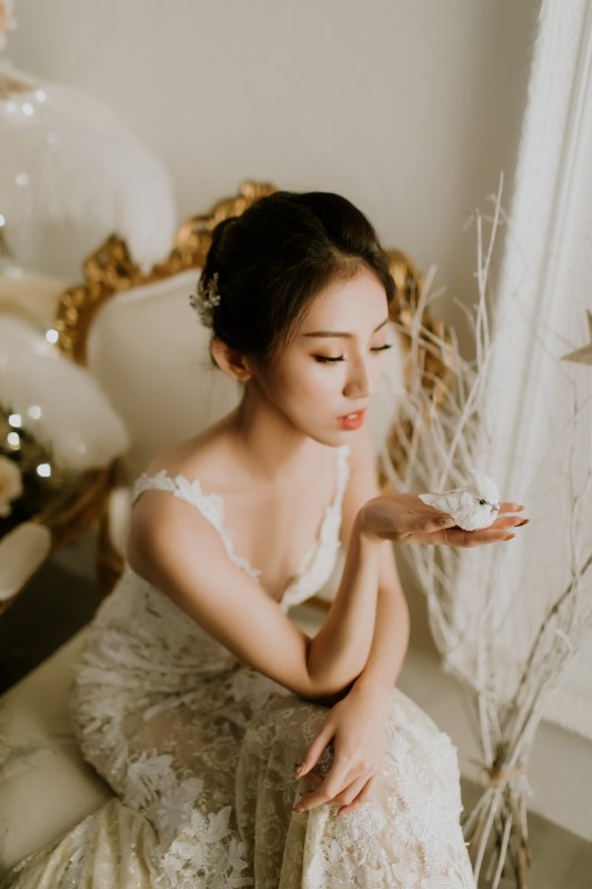 Dreamy White Wedding bride sitting on white and gold chair with hand out palm up holding a white bird