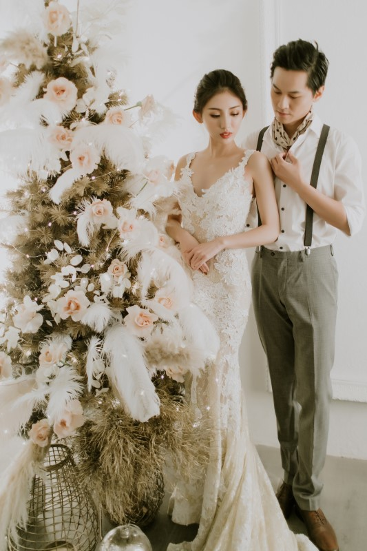 Dreamy White Wedding bride and goom standing next to frosted pine tree decorated with flowers