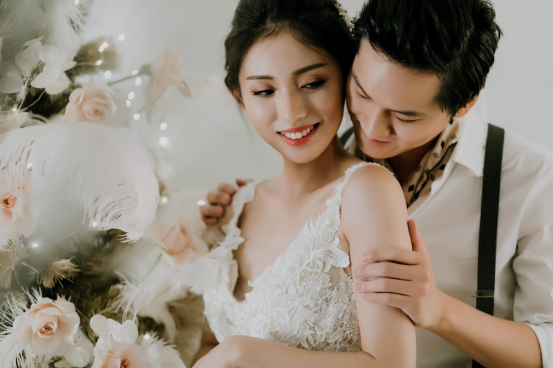 Dreamy White Wedding groom holding smilling bride with feather in her hand