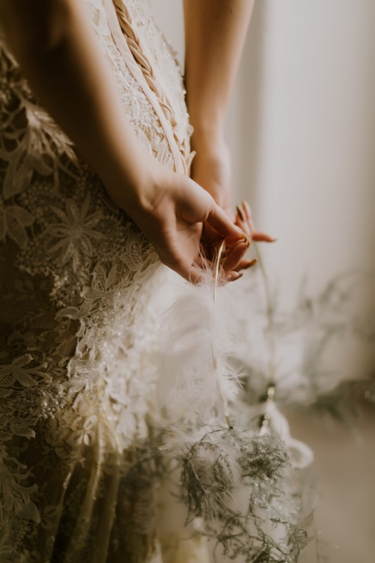 Dreamy White Wedding hands behind bride's back holding a feather