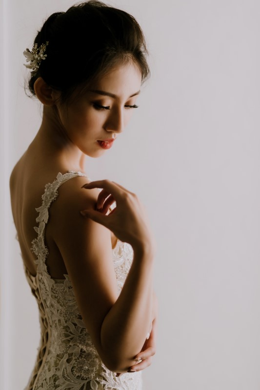 Dreamy White Wedding bride in lace gown touching her shoulder looking down