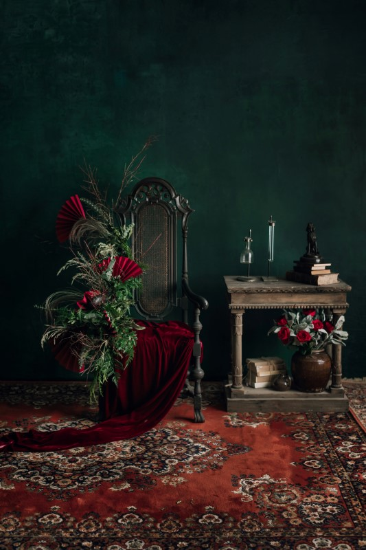 West Coast Weddings Magazine green wall, Persian rug, chair, table and floral arrangement with red fans Blushing Vintage Rentals