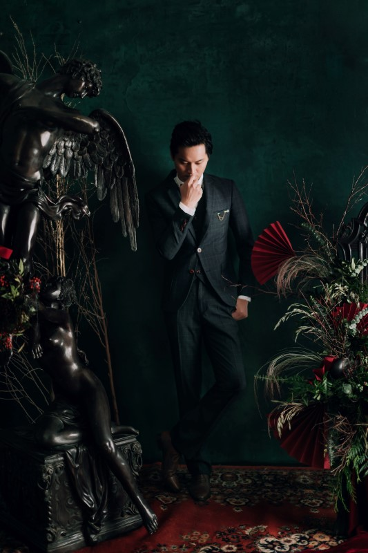Culture Fusion groom thinking pose next to black angel statue and greenery arrangement