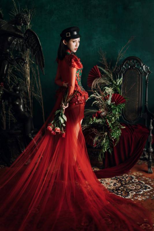 West Coast Weddings Magazine bride in red gown looking over her shoulder holdingm bouquet of red roses next to floral arrangement with red fans