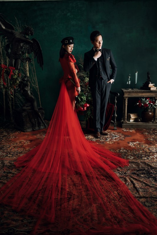 Culture Fusion bride in red dress with really long train laid out, groom next to her fixing his tie