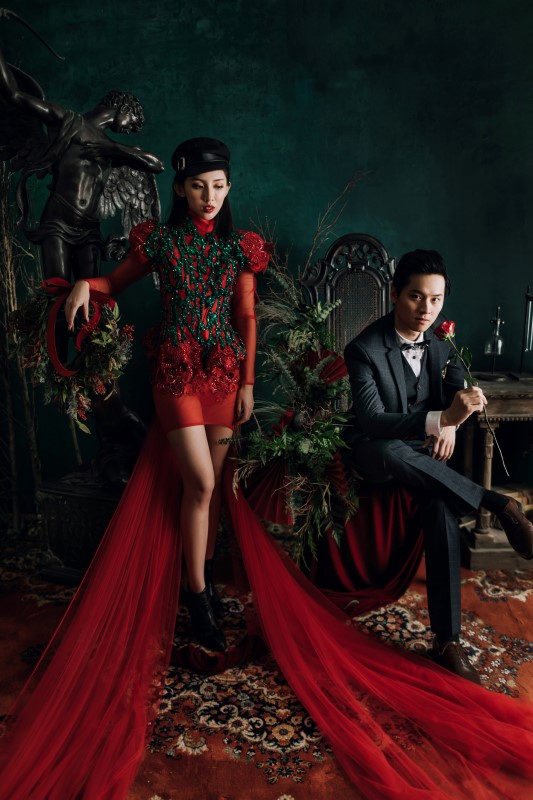 Culture Fusion bride in red gown with long train standing next to black angel statue, groom sitting on chair next to her