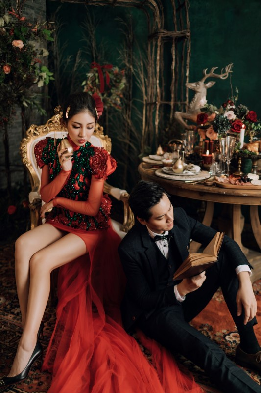Culture Fusion bride in red dress sitting on chair looking down at groom sitting on the ground reading a book