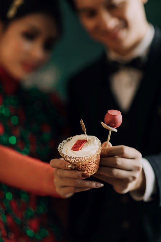 Culture Fusion bride and groom holding up dessert cup and cake pop