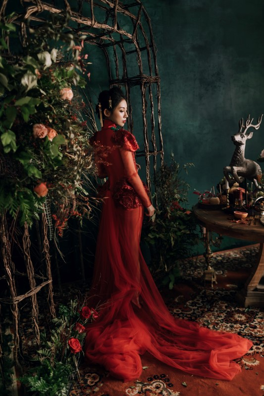 Culture Fusion bride in red gown with train standing next floral arrangements with orange roses