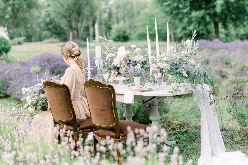 Bride seated at floral table in field of lavender in Vancouver